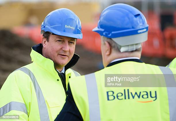 British Prime Minister David Cameron speaks to Bellway Chief Executive Ted Ayres during a visit to a Bellway housing development in Barking on...