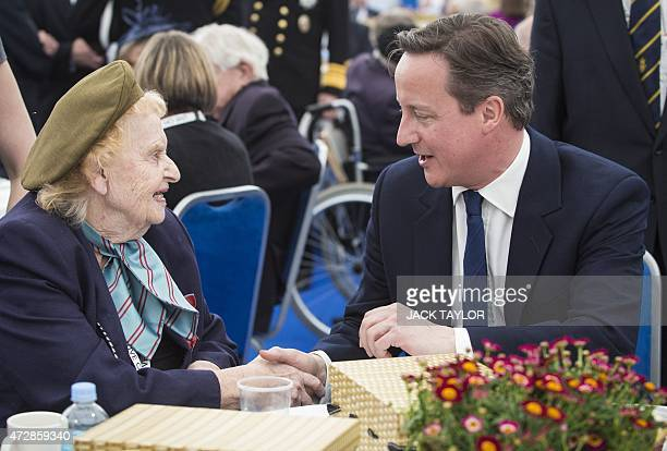 British Prime Minister David Cameron speaks with Helen Taylor Thompson a WWII First Aid Nursing Yeomanry veteran in London on May 10 during an event...