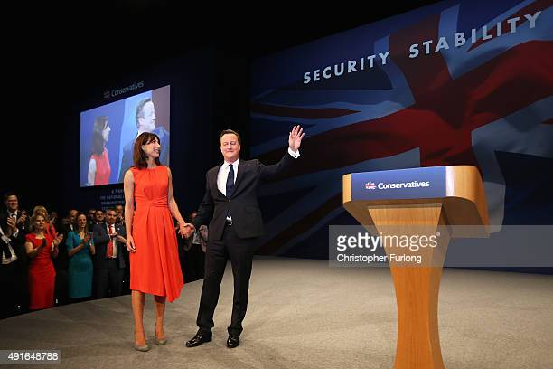 British Prime Minister David Cameron stands onstage with wife Samantha following his keynote speech to delegates on the fourth and final day of the...