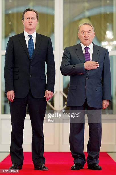 British Prime Minister David Cameron stands with Kazakhstan President Nursultan Nazarbayev as they listen to the national anthem at the Presidential...