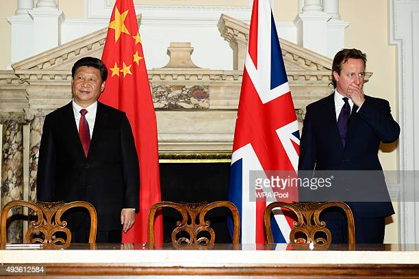 British Prime Minister David Cameron stands with the President of the People's Republic of China Xi Jinping during a commercial contract exchange at...