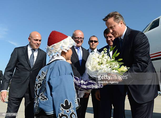 British Prime Minister David Cameron talks to a Turkish kid who presented flowers to him upon his arrival at the Antalya International Airport for...