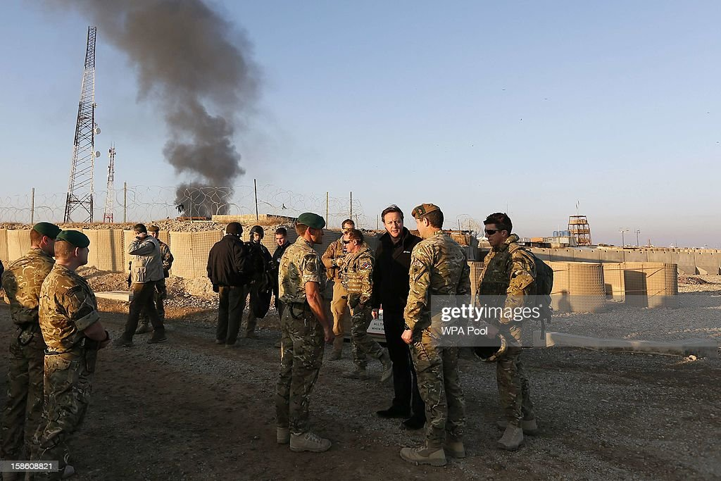 British Prime Minister David Cameron (3rd R) talks to British soldiers during a visit to Forward Operating Base Price on December 20, 2012 in Helmand Province, Afghanistan. Prime Minister Cameron is making a Christmas visit to British troops in the region amid tight security.