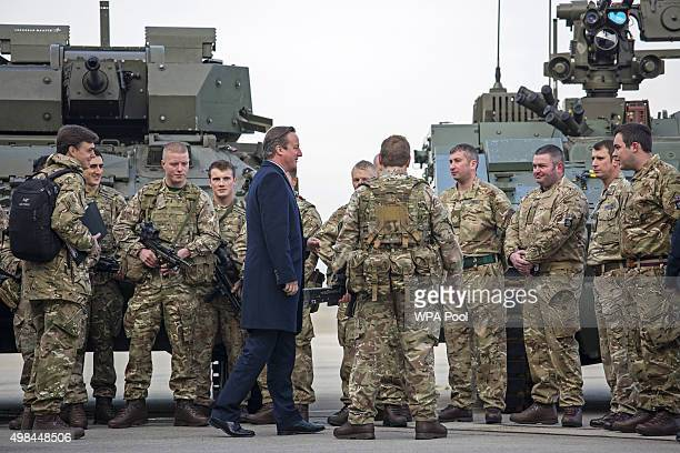 British Prime Minister David Cameron talks with soldiers from the Royal Welsh Infantry as they stand in front of a Lockheed Martin Warrior Infantry...