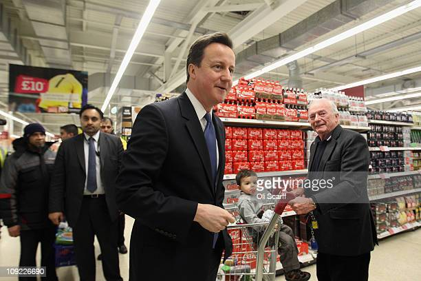 British Prime Minister David Cameron visits a branch of Sainsbury's supermarket with Work and Pensions Secretary Iain Duncan Smith on February 17...