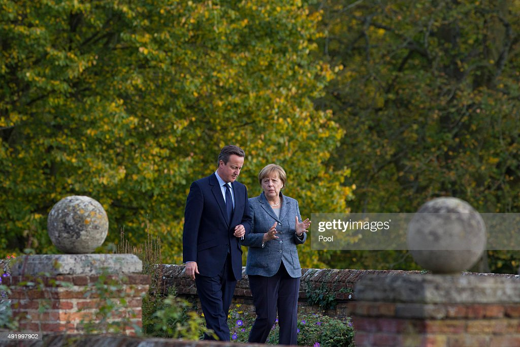 British Prime Minister David Cameron walks around the rose garden with German Chancellor Angela Merkel (R) during a meeting at Chequers, the Prime Minister's country residence on October 9, 2015 near Aylesbury, Buckinghamshire, United Kingdom. The meeting between the two leaders is expected to focus on Britain's EU renegotiation aims.