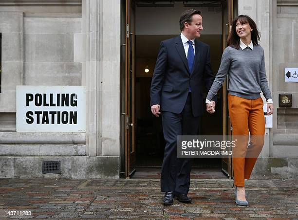 British Prime Minister David Cameron walks handinhand with his wife Samantha as he leaves a polling station in London on May 3 after casting his vote...