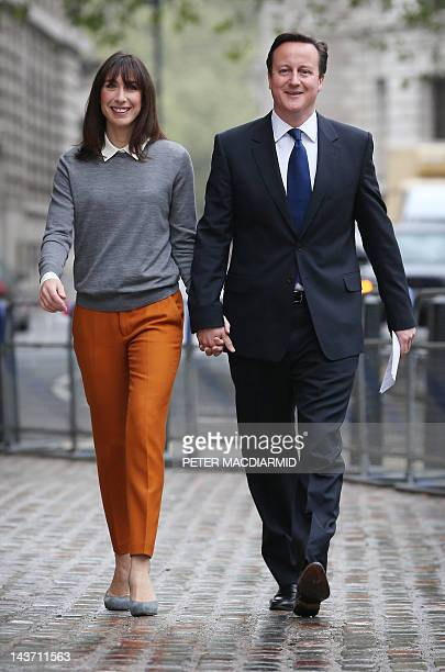 British Prime Minister David Cameron walks handinhand with his wife Samantha as he arrives at a polling station in London on May 3 after casting his...