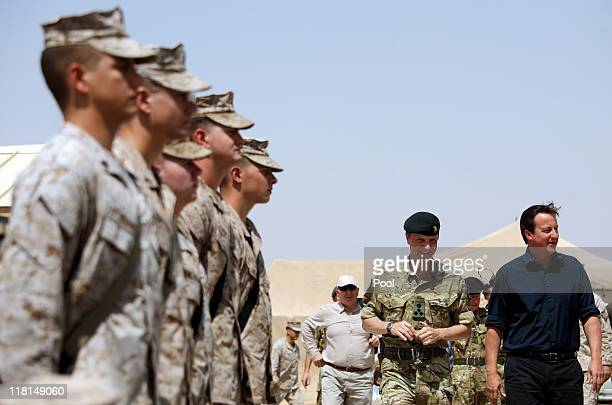 British Prime Minister David Cameron walks past troops as he arrives to address British and American troops at Camp Leatherneck military base on July...