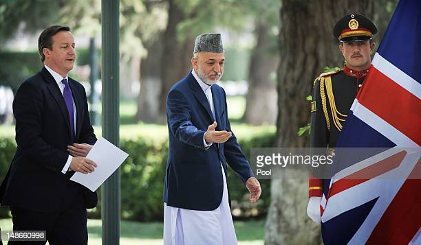British Prime Minister David Cameron walks with Afghan President Hamid Karzai before arriving at the Presidential Palace on July 19 2012 in Kabul...