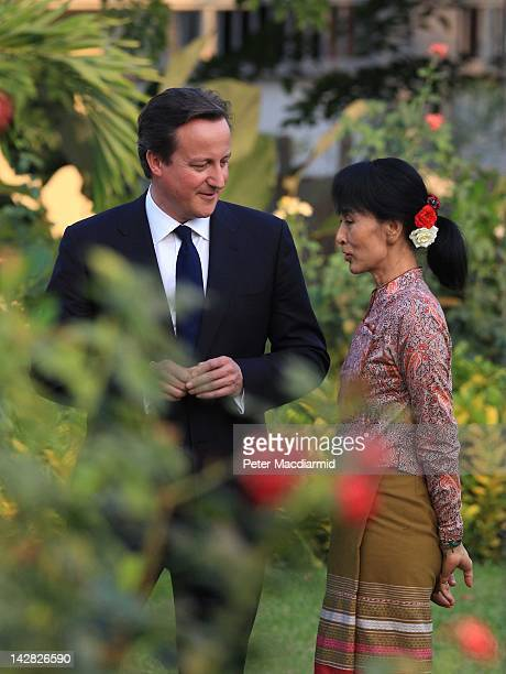 British Prime Minister David Cameron walks with prodemocracy leader Aung San Suu Kyi in her garden on April 13 2012 in Yangon Myanmar Mr Cameron is...