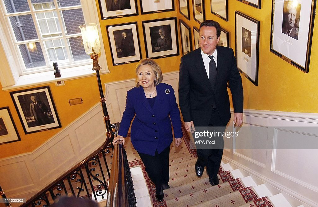 British Prime Minister David Cameron (R) walks with U.S. Secretary of State Hillary Clinton inside 10 Downing Street on March 29, 2011 in London, England. A summit consisting of 40 governments and international bodies have gathered in London to improve ties with the Libyan National Council, the umbrella group representing rebel Libyan forces, and in preparation for the intended aim of ending of the reign of Libyan leader Muammar Gaddafi.
