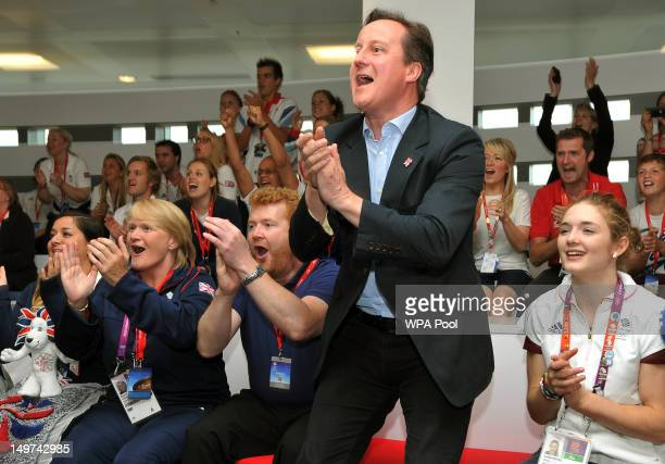 British Prime Minister David Cameron watches the gold medal winning GB rowers at Eton Dorney with Ian Pinches and his daughter Jennifer on August 3...