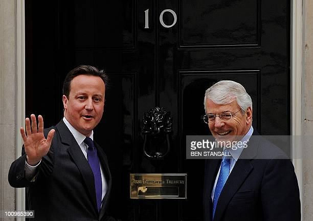 British Prime Minister David Cameron waves as he greets former British Prime Minister John Major on the steps of 10 Downing Street in central London...