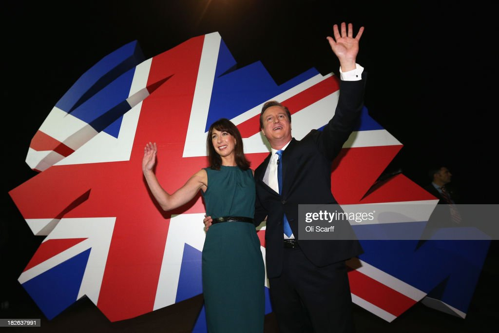 British Prime Minister David Cameron waves to the audience with his wife Samantha after delivering his keynote speech on the last day of the annual Conservative Party Conference at Manchester Central on October 2, 2013 in Manchester, England. During his closing speech David Cameron will say that his 'abiding mission' would make the UK into a 'land of opportunity'.