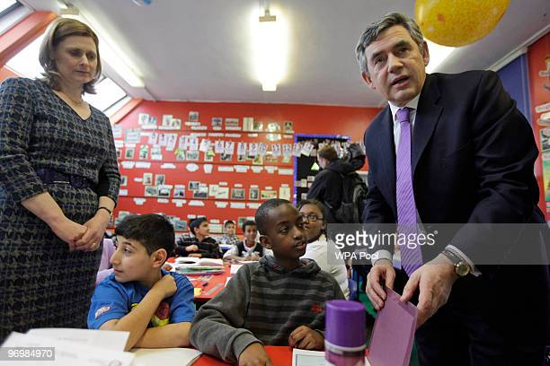 British Prime Minister Gordon Brown center accompanied by his wife Sarah right and Education minister Ed Balls seated 2nd left visits a classroom at...