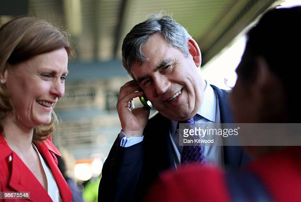 British Prime Minister Gordon Brown speaks to the friend of a commuter on her phone at Southampton train station as his wife Sarah Brown looks on on...