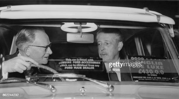 British Prime Minister Harold Macmillan in a new Ford Anglia with Sir Patrick Hennessy chairman of Ford of Britain after opening the 1959 Motor Show...