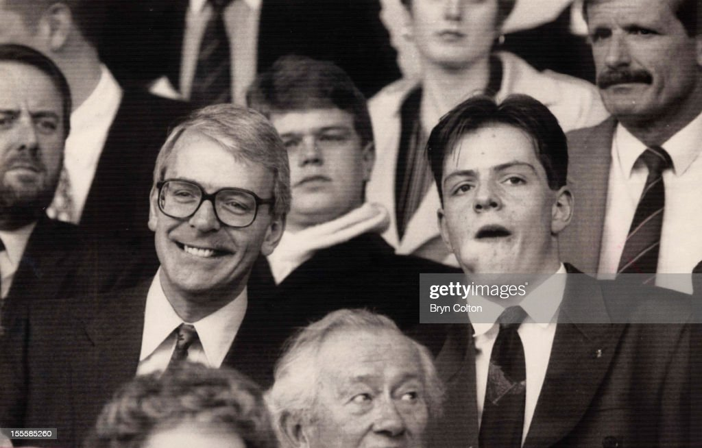 British Prime Minister John Major (left) and his son James watching a football match between Norwich City and Manchester United at Carrow Road, Norwich, 30th March 1991.