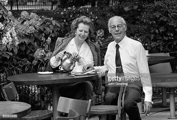 British prime minister Margaret Thatcher and her husband Denis enjoy a cup of tea al fresco while Denis smokes a cigarette circa 1985