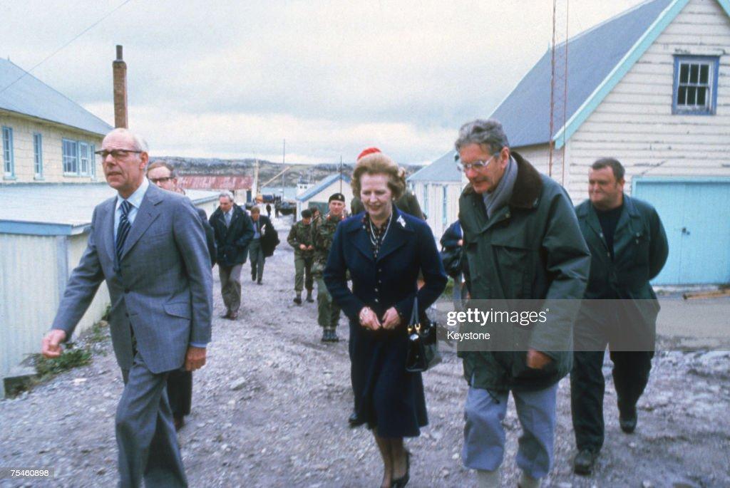 British Prime Minister Margaret Thatcher and her husband Denis (1915 - 2003, left) visit Stanley Junior School, Stanley in the Falkland Islands, 1983.