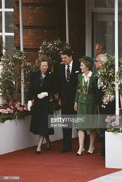 British Prime Minister Margaret Thatcher and her husband Denis Thatcher walk with US President Ronald Reagan and his wife Nancy Reagan as they arrive...