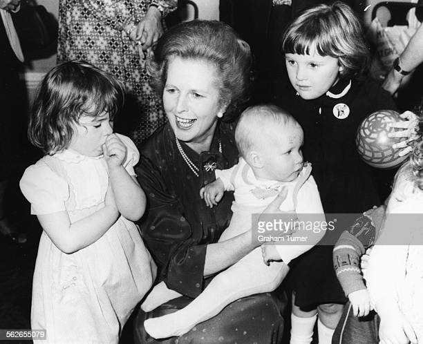 British Prime Minister Margaret Thatcher holding ten month old baby Adam Wood on her lap as she meets a group of children the sons and daughters of...