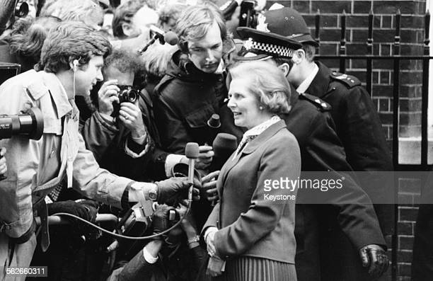 British Prime Minister Margaret Thatcher is escorted by policemen as she talks to the press while arriving to commence her first day in office at 10...