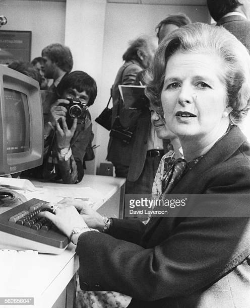 British Prime Minister Margaret Thatcher is photographed by the press as she tries out a word processing system computer during a visit to Logica Ltd...
