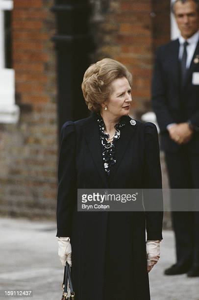 British Prime Minister Margaret Thatcher stands on the red carpet as she awaits the arrival of US President Ronald Reagan for the start of the...
