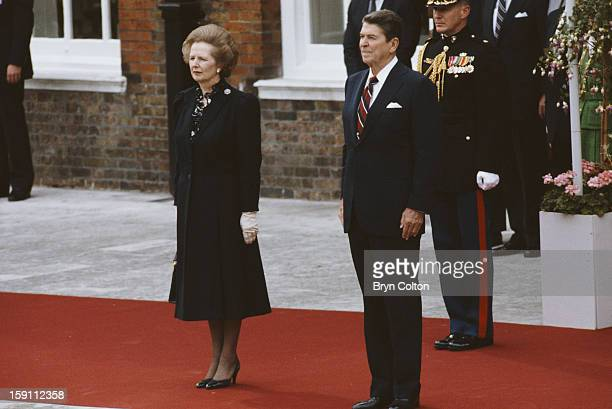 British Prime Minister Margaret Thatcher stands with US President Ronald Reagan , as they listen to the American national anthem at Kensington Palace...