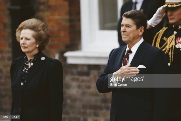 British Prime Minister Margaret Thatcher stands with US President Ronald Reagan as they listen to the American national anthem at Kensington Palace...