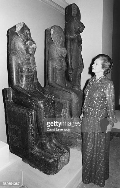 British Prime Minister Margaret Thatcher viewing a series of black granite figures of the goddess Sakhmet from Thebes at the Egyptian Sculpture...