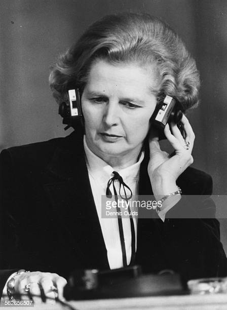 British Prime Minister Margaret Thatcher wearing headphones as she listens to the translated speech of Italian Prime Minister Cossiga, at Church...