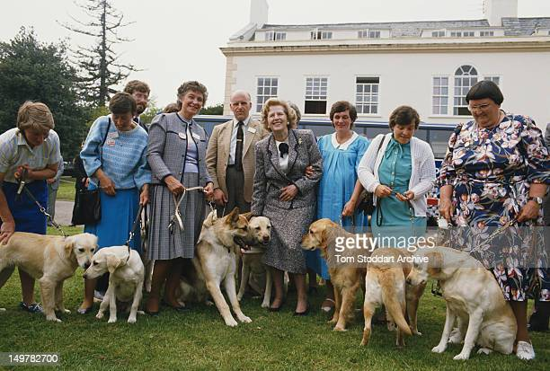 British Prime Minister Margaret Thatcher with a group of blind people and their guide dogs, during the UK general election campaign, 1987.