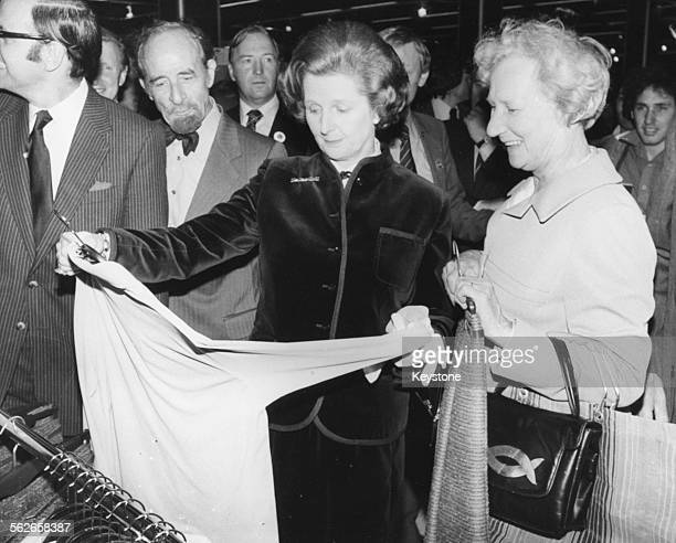 British Prime Minister Margaret Thatcher with GLC Chairman Sir Horace Cutler inspecting a shirt with a local woman during a tour of the new £45...