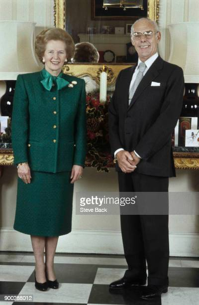 British Prime Minister Margaret Thatcher with her husband Denis Thatcher stands in the entrance hall of No10 Downing Street the official residence of...