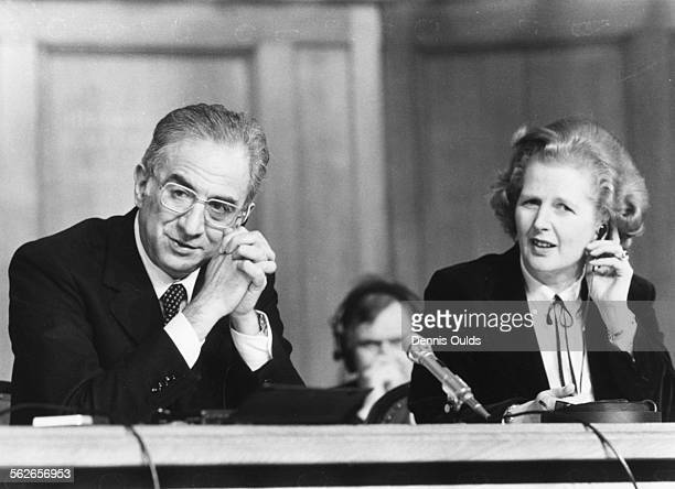 British Prime Minister Margaret Thatcher, with translation headphones, and Italian Prime Minister Francesco Cossiga at a joint press conference...