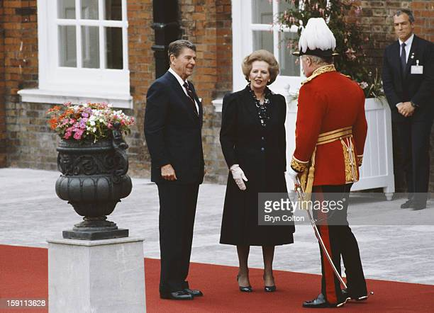 British Prime Minister Margaret Thatcher with US President Ronald Reagan as they arrive for the opening ceremony at Kensington Palace Gardens for the...