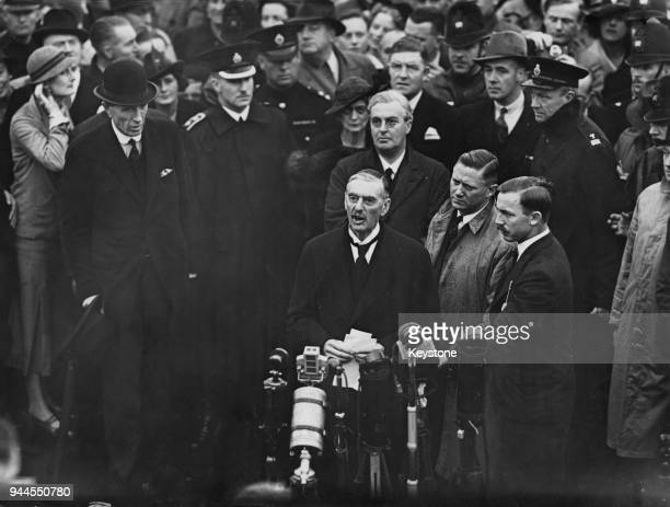 British Prime Minister Neville Chamberlain addresses the crowds at Heston Aerodrome upon his return to England from Munich after talks with Adolf...