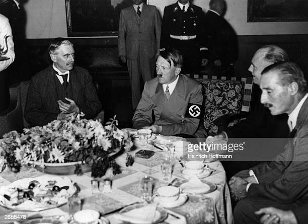 British prime minister Neville Chamberlain and Adolf Hitler with his interpreter Paul Schmidt and Neville Henderson at dinner during Chamberlain's...