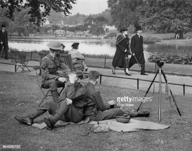 British Prime Minister Neville Chamberlain and his wife Anne pass a group of army signallers at practice during their morning walk in the park London...