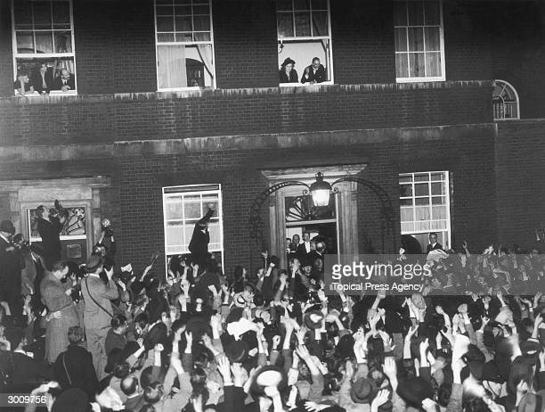 British Prime Minister Neville Chamberlain and his wife look down from a window at 10 Downing Street as crowds gather to applaud his peacemaking...