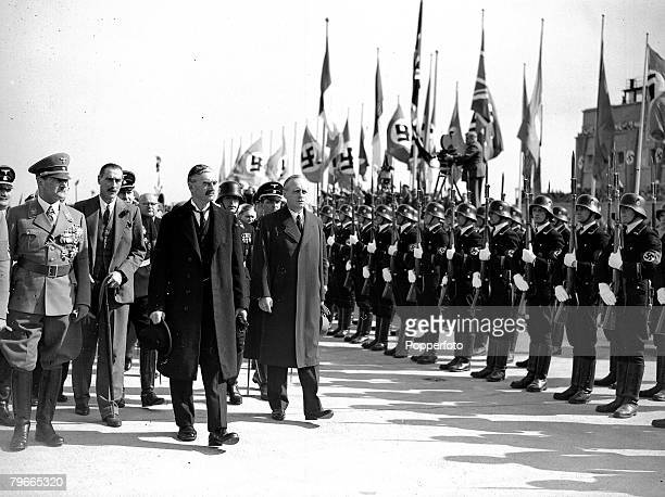 British Prime Minister Neville Chamberlain passes a Nazi honour guard on his arrival at Oberwiesenfeld airport before a meeting with Adolf Hitler...