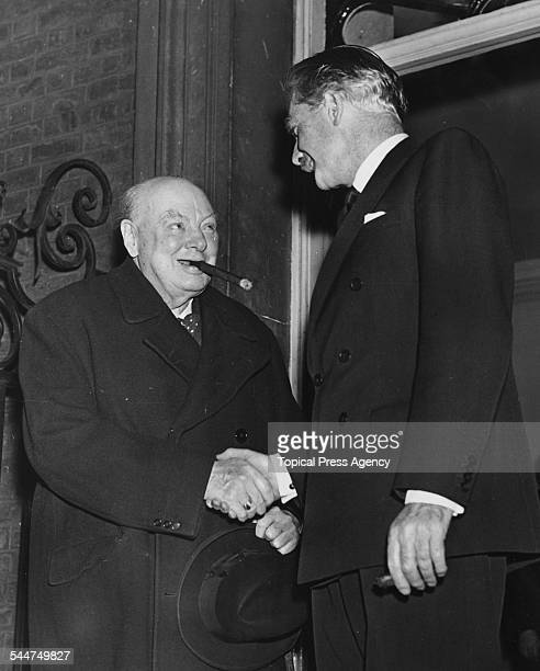 British Prime Minister Sir Anthony Eden shaking hands with former Prime Minister Sir Winston Churchill outside 10 Downing Street after a meeting...