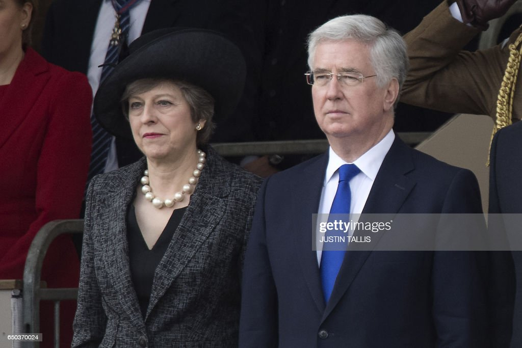 British Prime Minister Theresa May (L) and British Defence Secretary Michael Fallon attend a Service of Commemoration and Drumhead Service on Horse Guards Parade in central London on March 9, 2017, which honours the service and duty of both the UK Armed Forces and civilians in the Gulf region, Iraq and Afghanistan, and those who supported them back home, from 1990-2015. After the Drumhead Service, The Queen will officially unveil The Iraq and Afghanistan memorial. / AFP PHOTO / Justin TALLIS