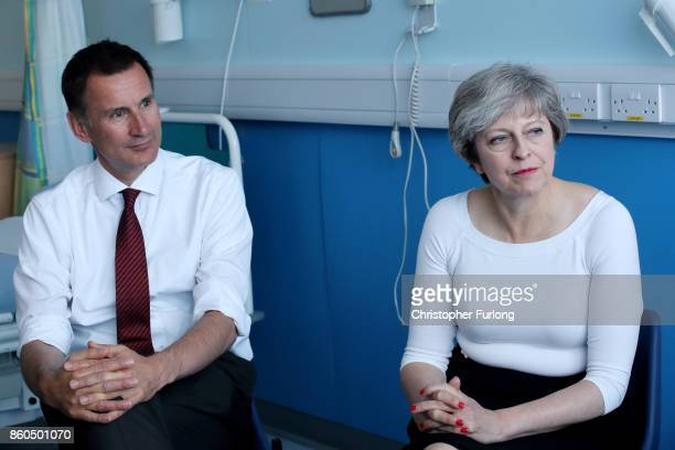 British Prime Minister Theresa May and British Secretary of State for Health Jeremy Hunt speak to patients during a round table discussion as they...
