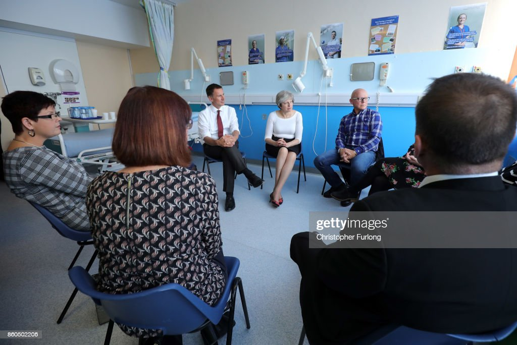 British Prime Minister Theresa May (C) and British Secretary of State for Health Jeremy Hunt (3rd R) speak to patients during a round table discussion as they visit the Renal Transplant Unit at the Royal Liverpool University Hospital on October 12, 2017 in Liverpool, England. The Prime Minister has proposed to include a new opt-out system for organ donation in England in an upcoming public consultation. There are still more people waiting for transplants than there are organs available. Currently organ donation is via an opt-in system with potential donors carrying a card.
