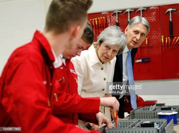 British Prime Minister Theresa May and Chancellor Of The Exchequer Philip Hammond chat to apprentices during a visit to the adi group on October 1...