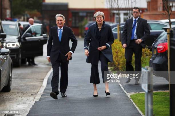 British Prime Minister Theresa May and Chancellor of the Exchequer Philip Hammond leave after visiting a home in Walkden near the Conservative...